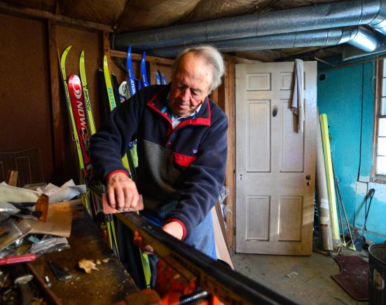 Caldwell uses an ordinary clothes iron to apply wax to his cross country skis. Photo by Kris Radder.