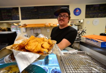 Jacob Friend holds an order of fresh chips, made on-site. Photo: Kristopher Radder.