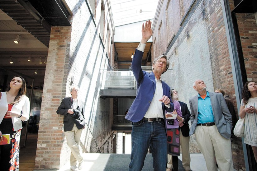 Joseph C. Thompson, founding director of Mass MoCA, points out the central light well in Building 6 of the Massachusetts Museum of Contemporary Art, during a tour. Berkshire Eagle File Photo