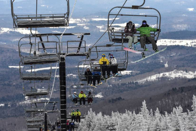 Skiers and snowboarders ascend the slope at Mount Snow in West Dover, Vt.