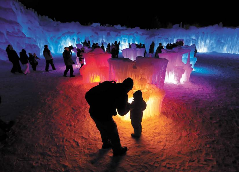 In this January 2019 photo, Bruce McCafferty and his son, Dougie, pause while exploring the ice formations growing at Ice Castles in North Woodstock, N.H.