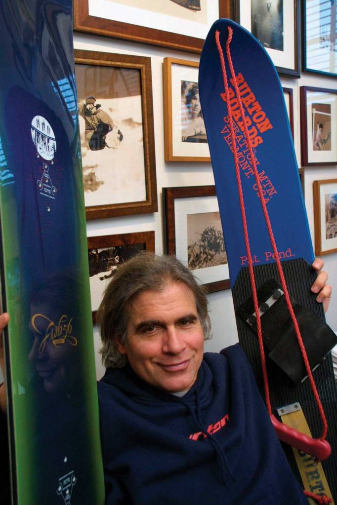 In this March 2002 file photo, Jake Burton Carpenter, owner of Burton Snowboards, shows an early model, right, and one of the newer snowboards, left, in his office in Burlington, Vt.